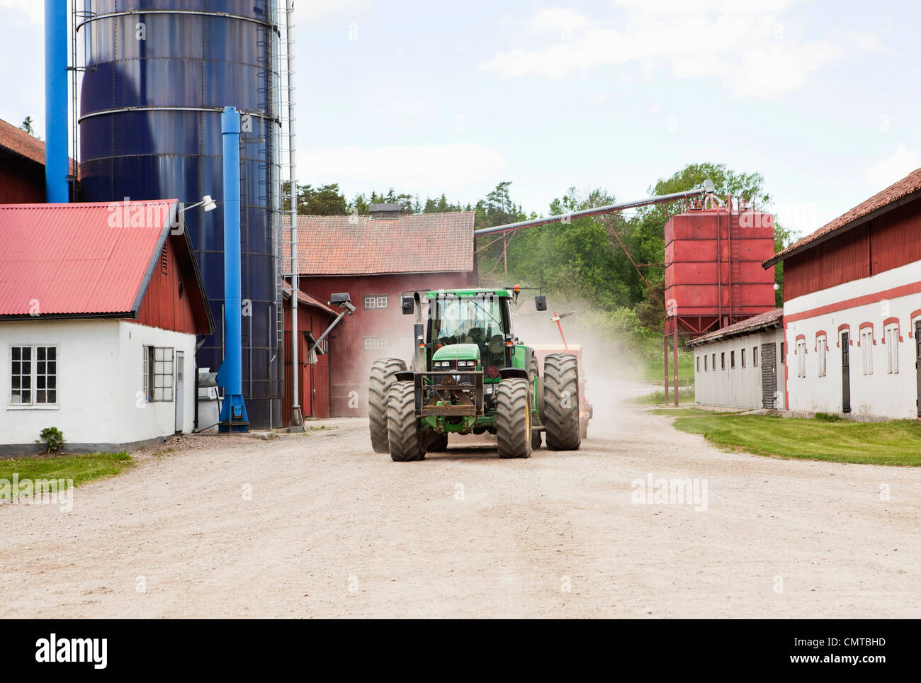 Tractor on the move on dirt road - Stock Image