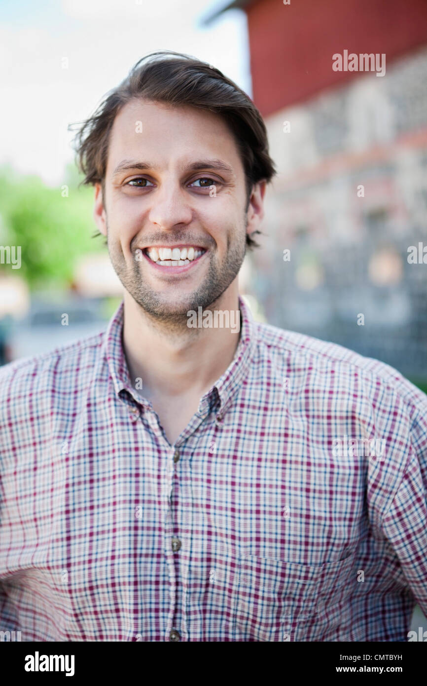 Portrait of young man wearing checked shirt - Stock Image