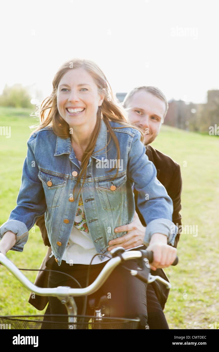 Happy couple riding bicycle - Stock Image