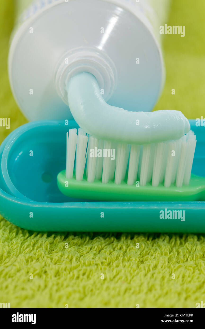 squeeze toothpaste and toothbrush on green towel - Stock Image