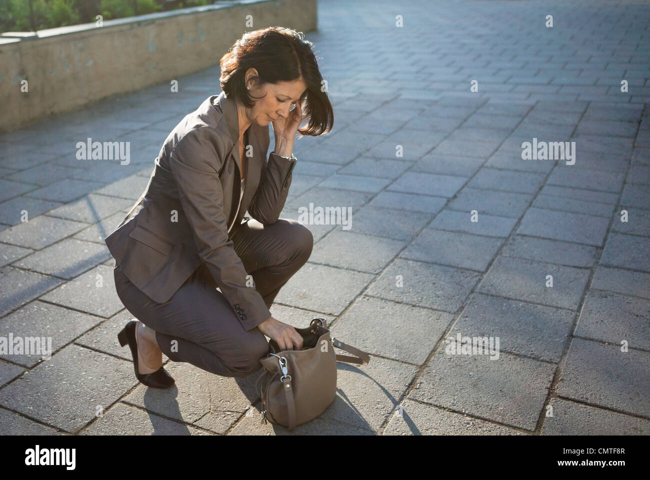 Businesswoman searching for something in handbag - Stock Image