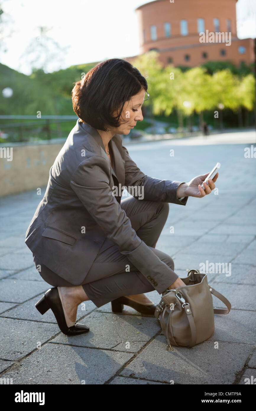 Woman searching for something in bag - Stock Image