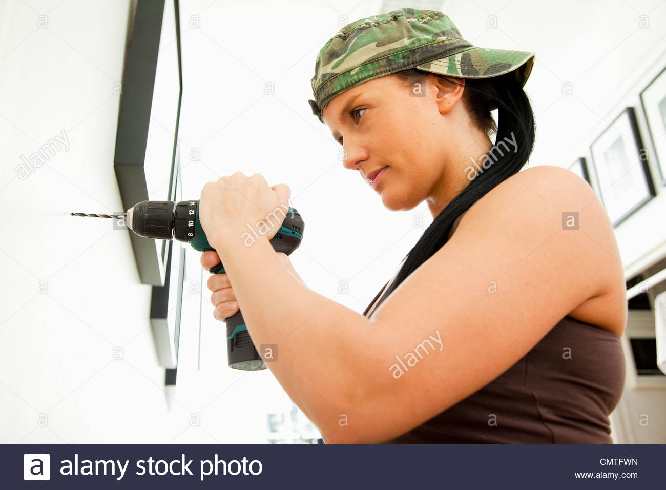Woman standing with drilling machine against the wall - Stock Image