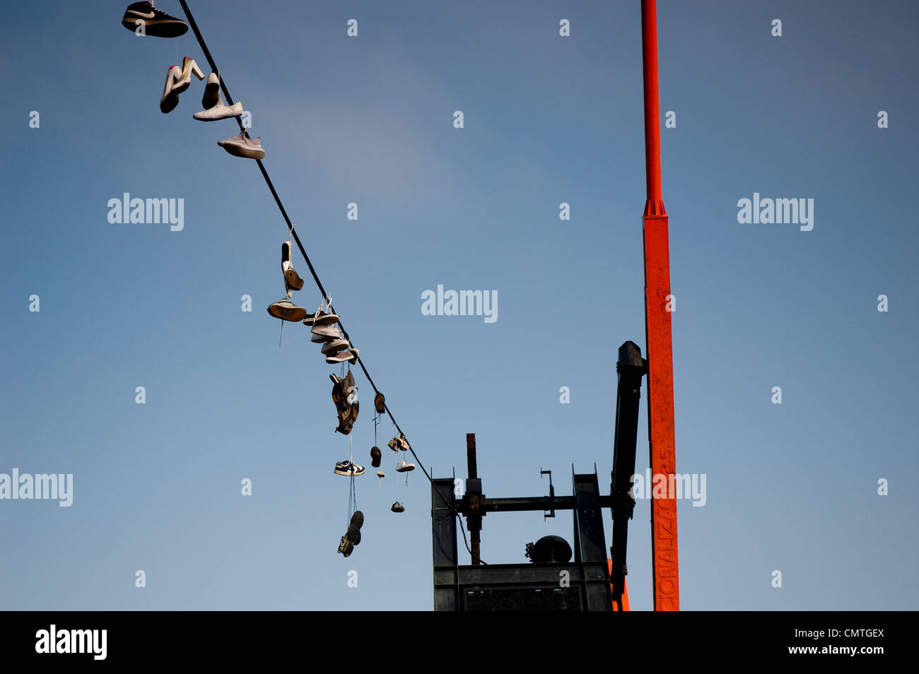 Shoes hanging on a cable of the metronome in Prague, Czech Republic - Stock Image