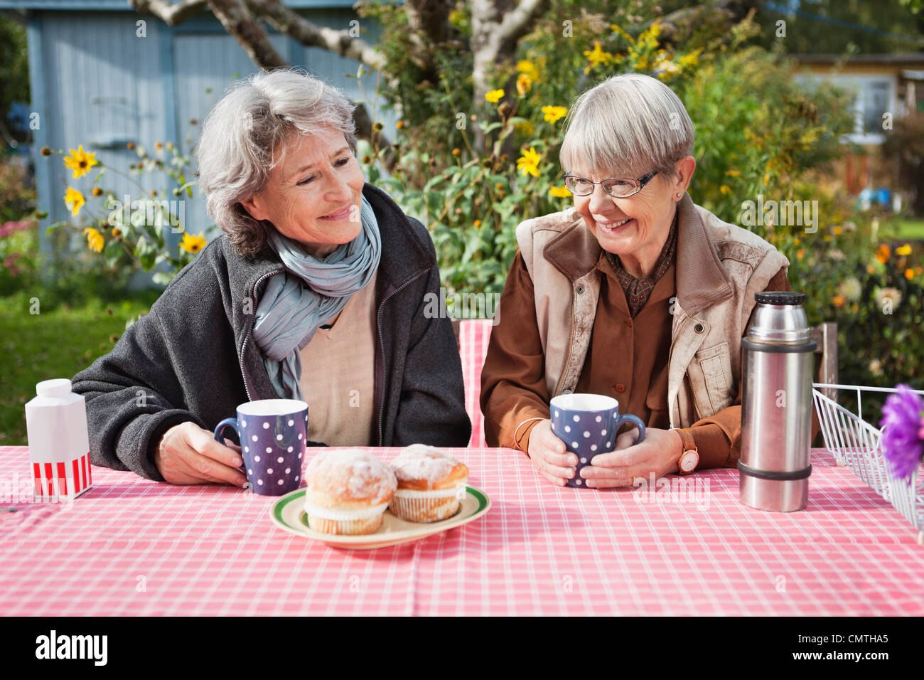 Two senior women drinks coffee at checkered table - Stock Image