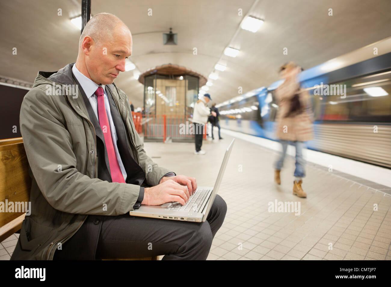 Man on platform using laptop - Stock Image