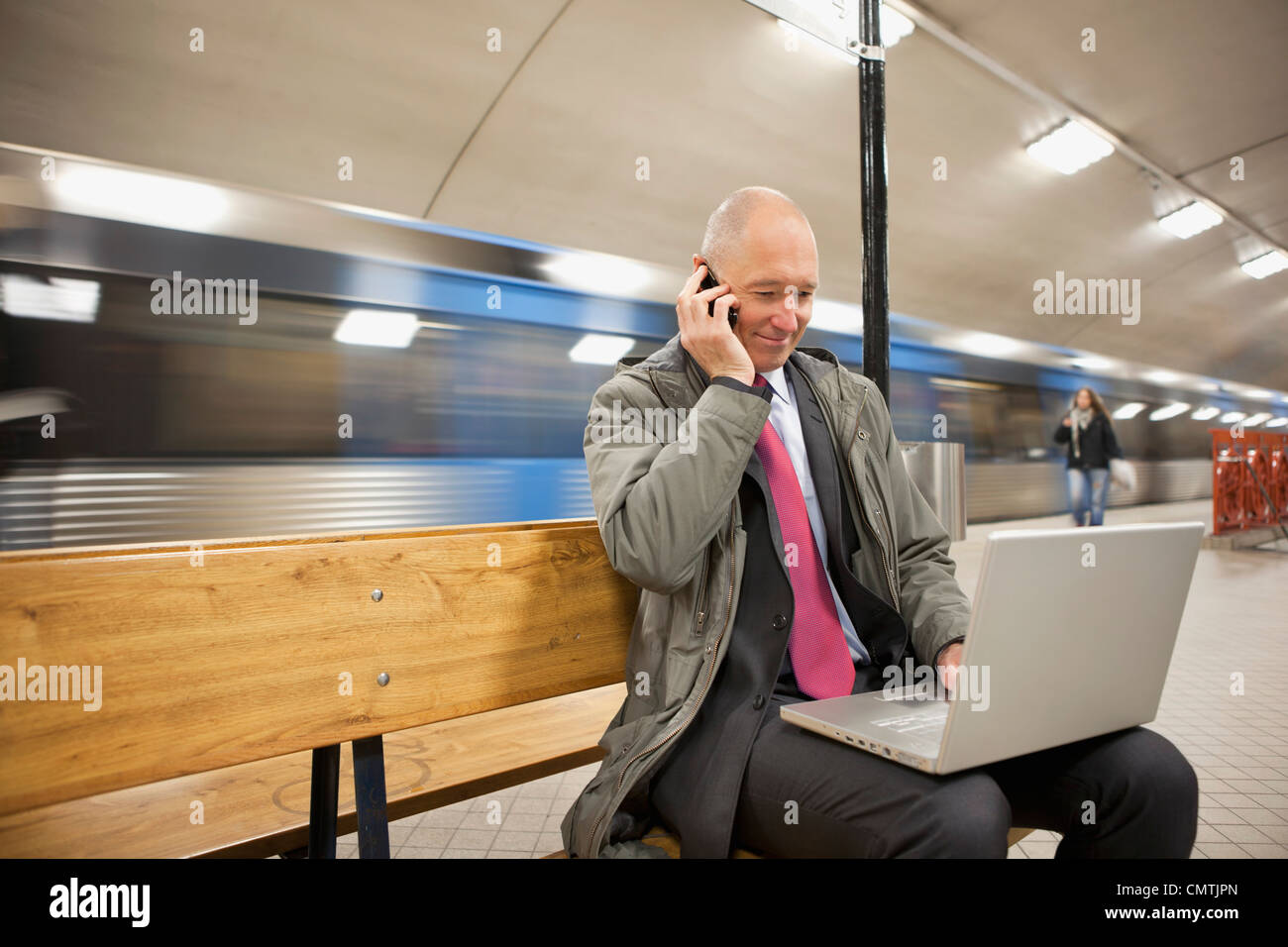 Man with laptop and cell phone on platform - Stock Image