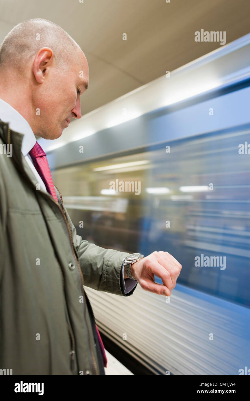 Businessman at train station checking the time - Stock Image