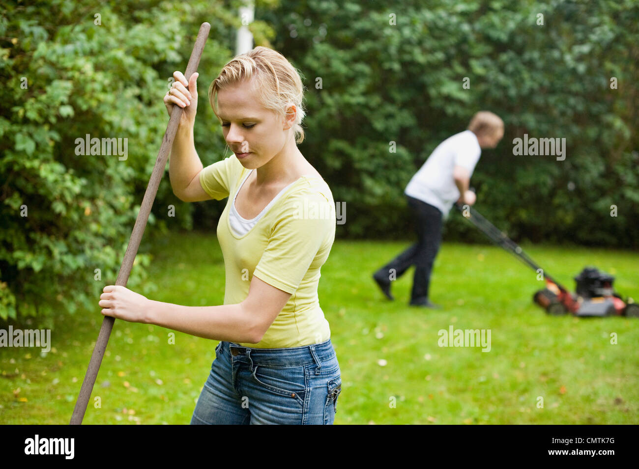 Woman with stick and man using manual lawn mower to cut grass - Stock Image