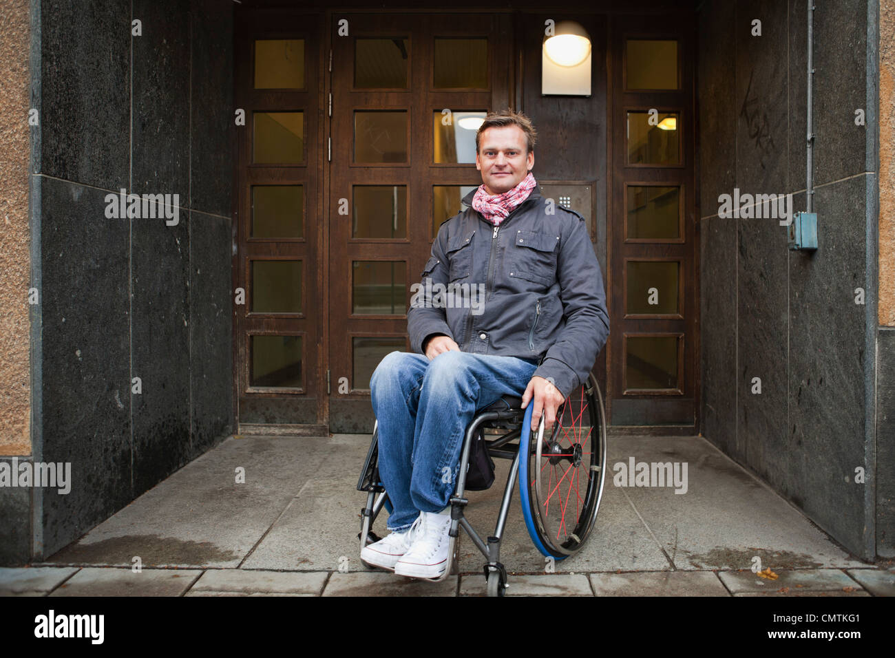 Man sitting in wheelchair looking at camera - Stock Image