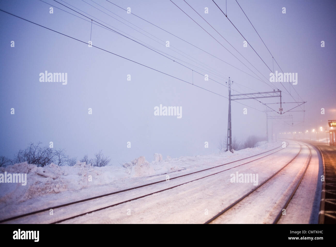 Snow-filled railway track a chilly winter evening - Stock Image