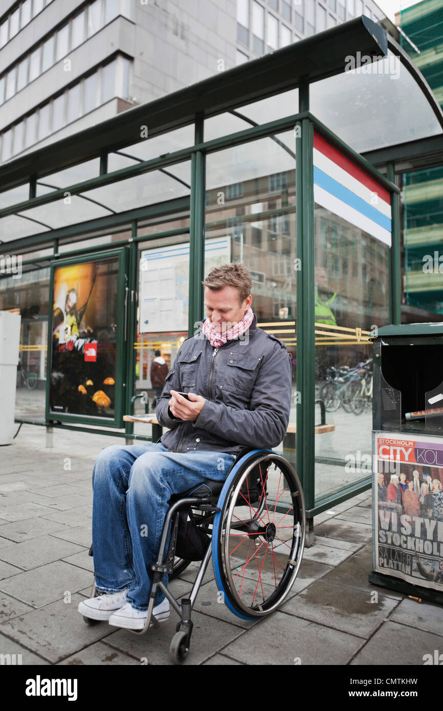 Man in wheelchair waiting for the bus - Stock Image