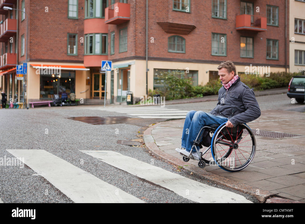 Man in wheelchair crossing road - Stock Image