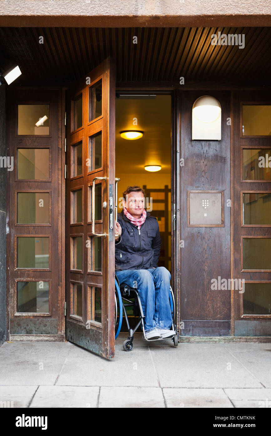 Man in wheelchair coming out - Stock Image