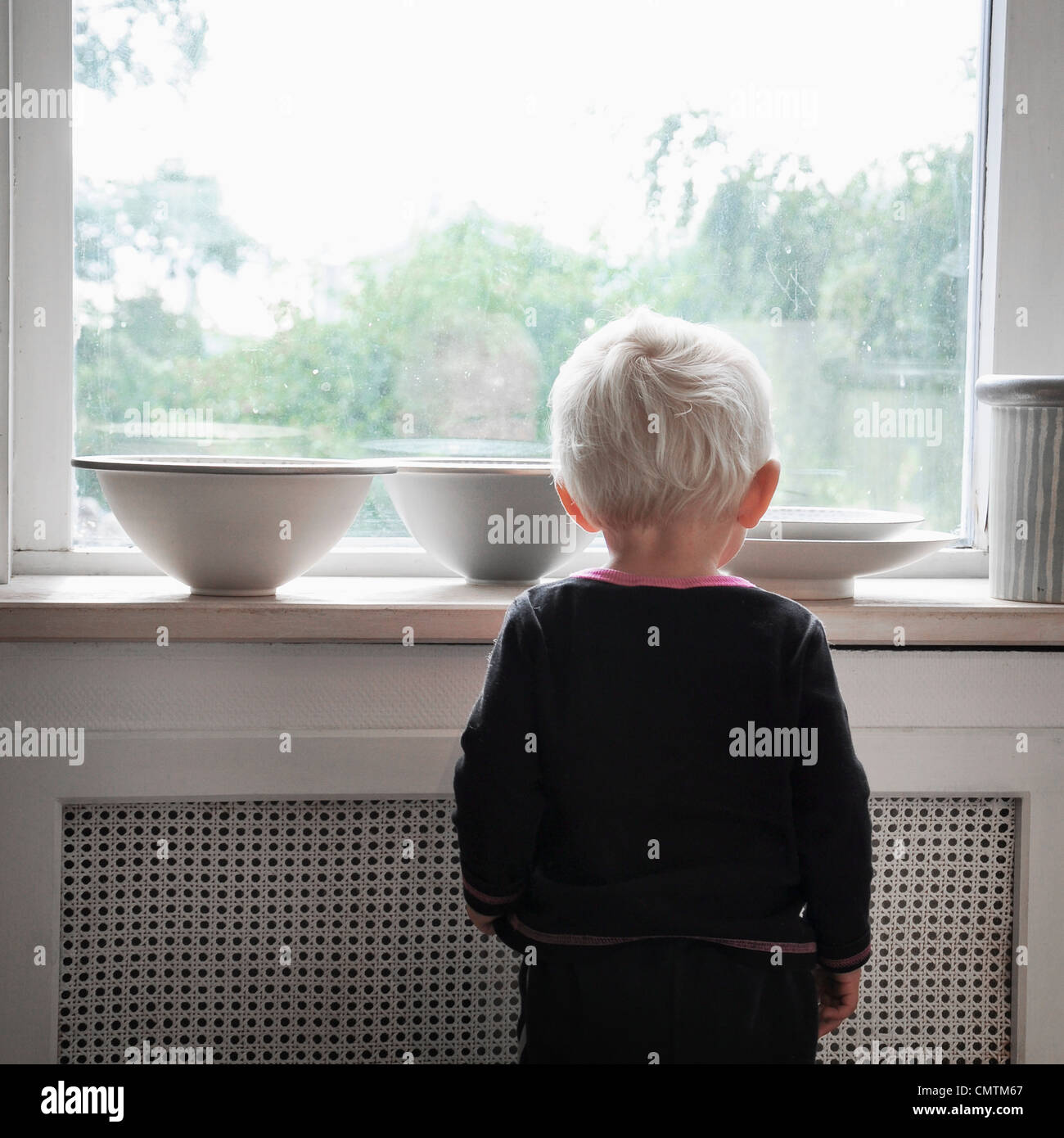 Small boy looking out through window - Stock Image