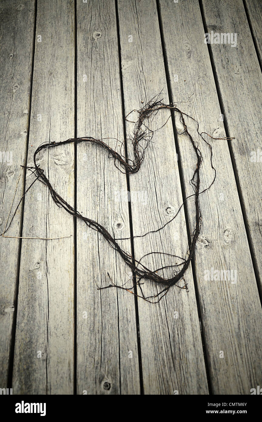 Lace lying on a wooden deck formed as a heart - Stock Image