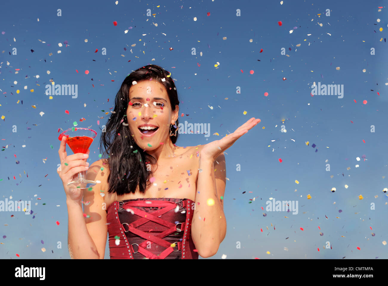 woman celebrating at party drinking cocktail - Stock Image