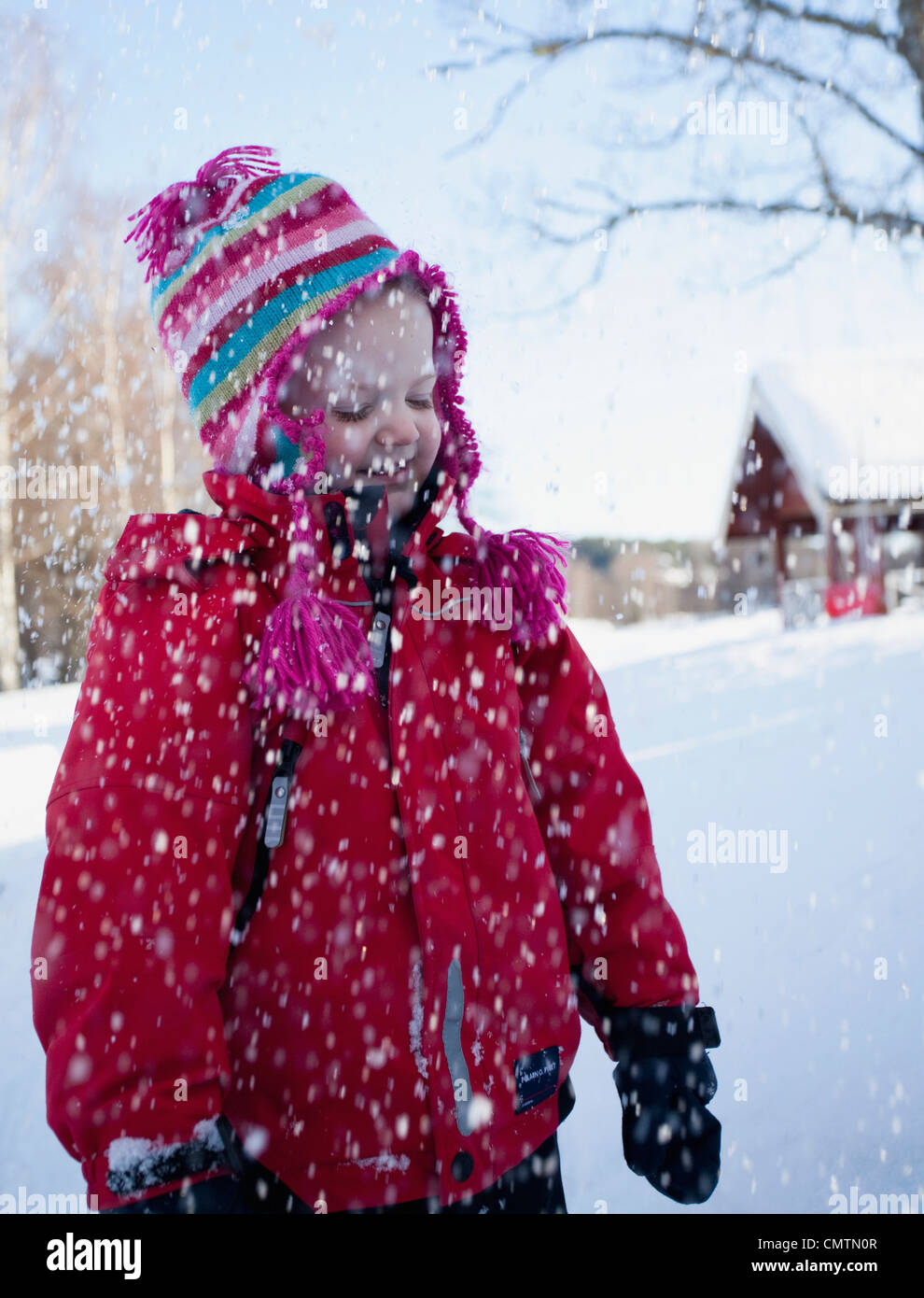 Girl (6-7) standing in snow fall - Stock Image
