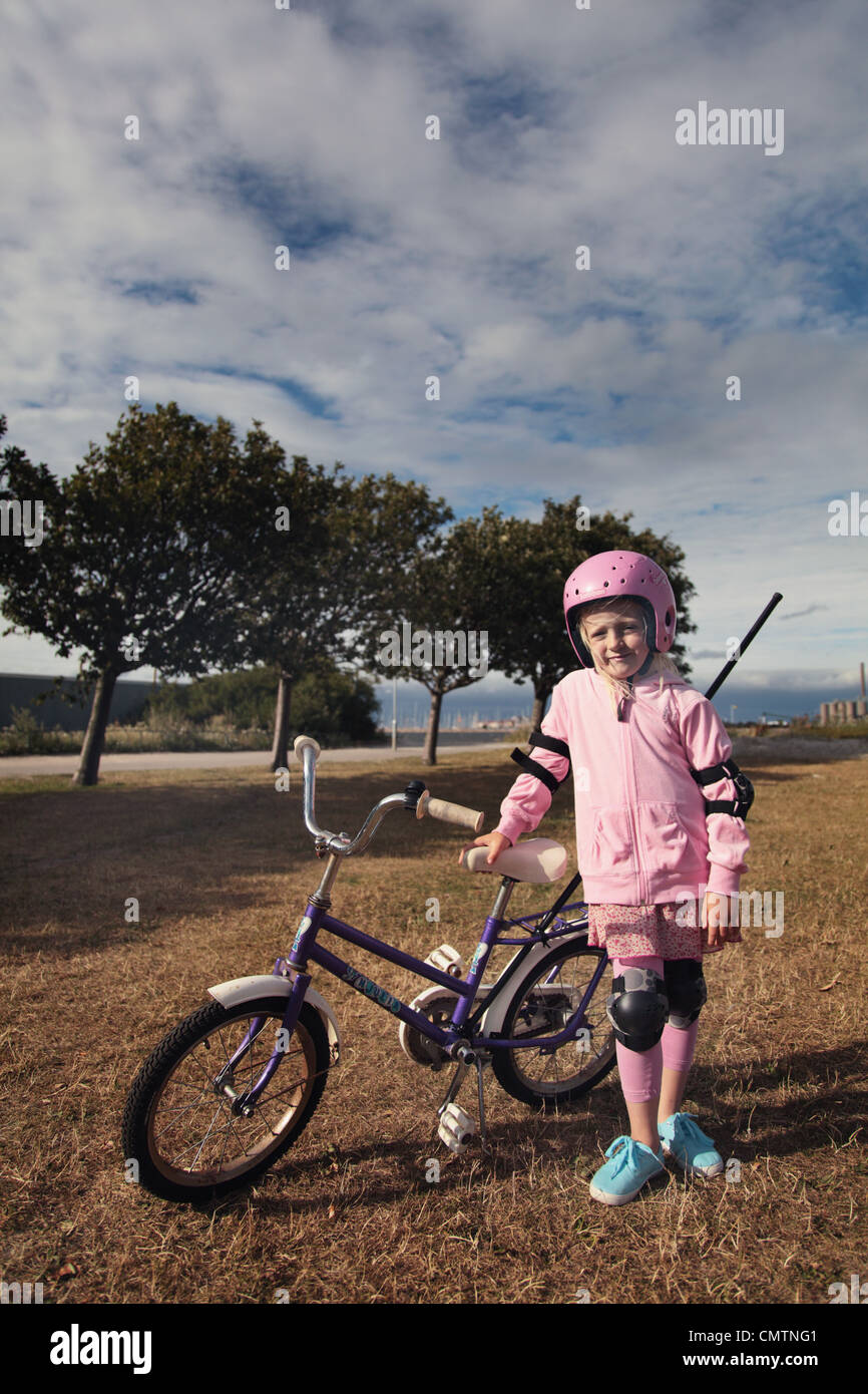 Girl (6-7) leaning on bicycle - Stock Image