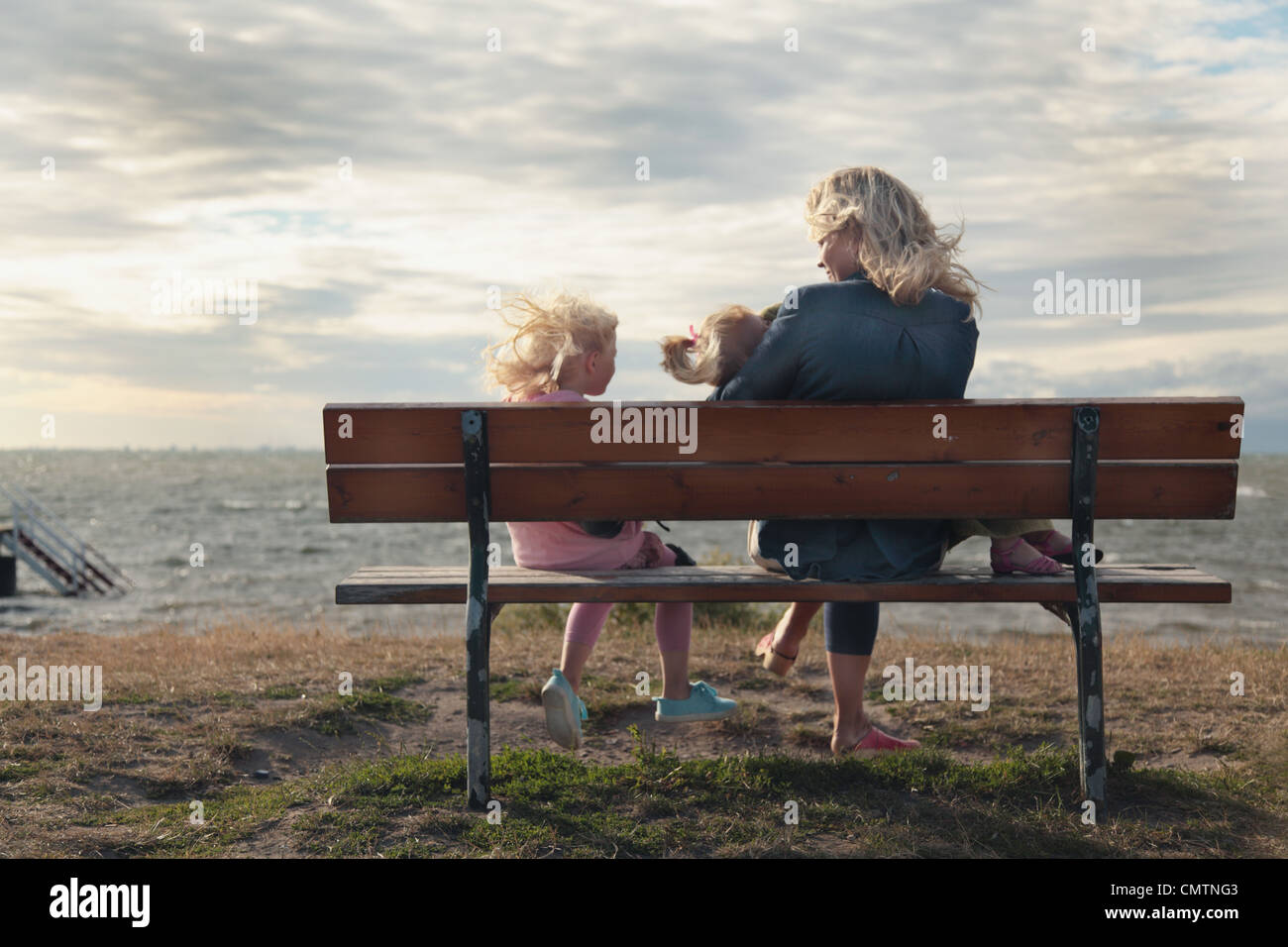 Woman and daughters (4-7) sitting on bench at beach - Stock Image