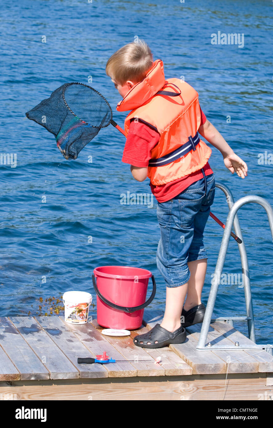 Young boy wearing a lifejacket catching fish with a landing net Stock Photo