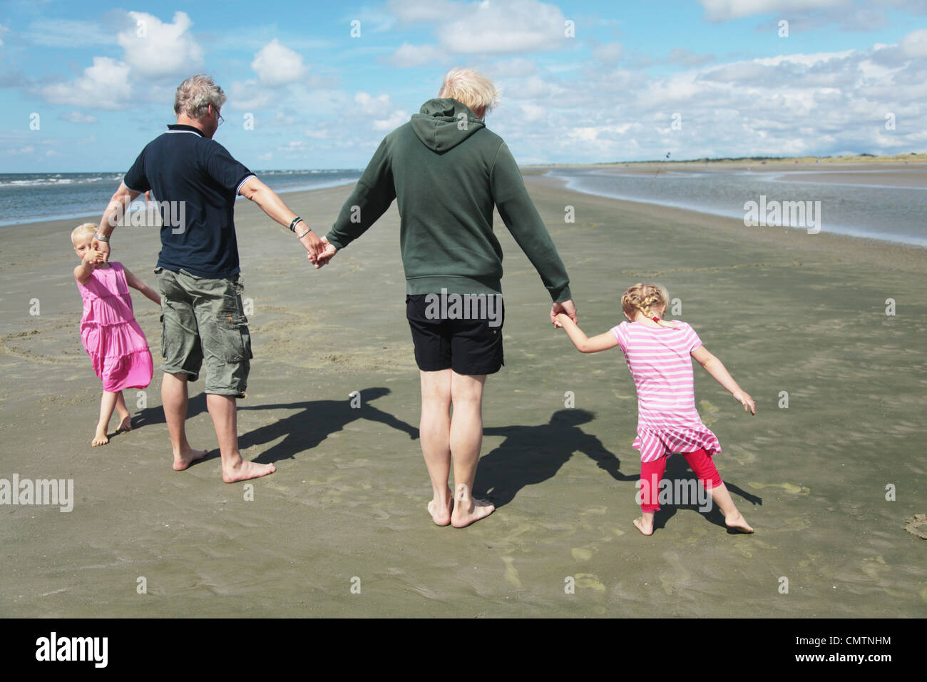 Rear view of parents and daughters (4-7) holding hands on beach - Stock Image