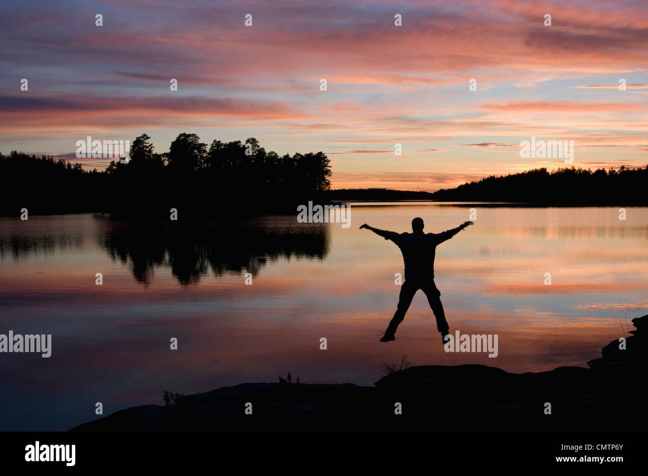 Man jumping in water at sunset - Stock Image