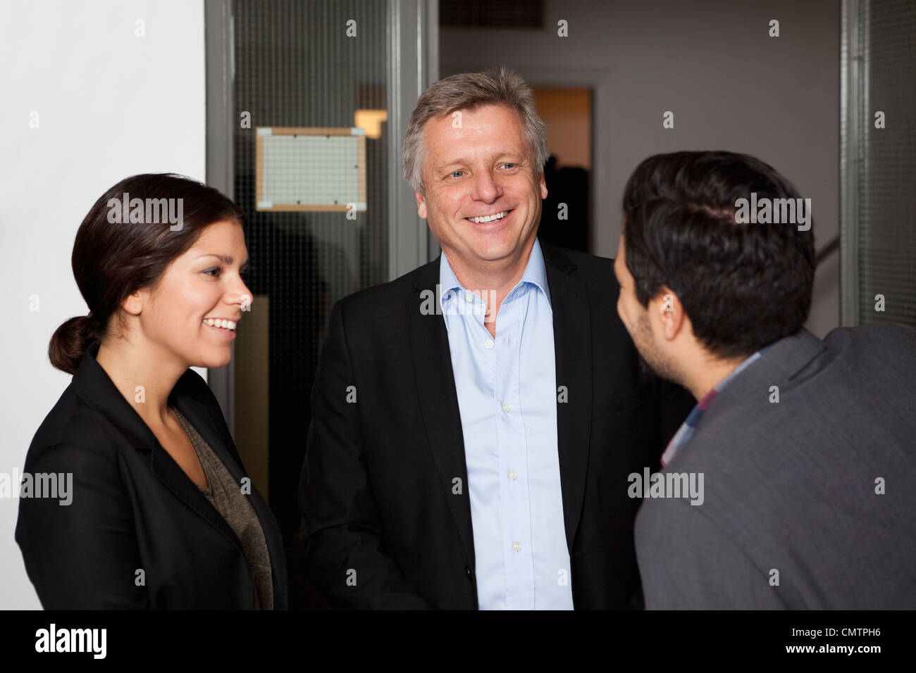 Three colleagues meet and laugh - Stock Image