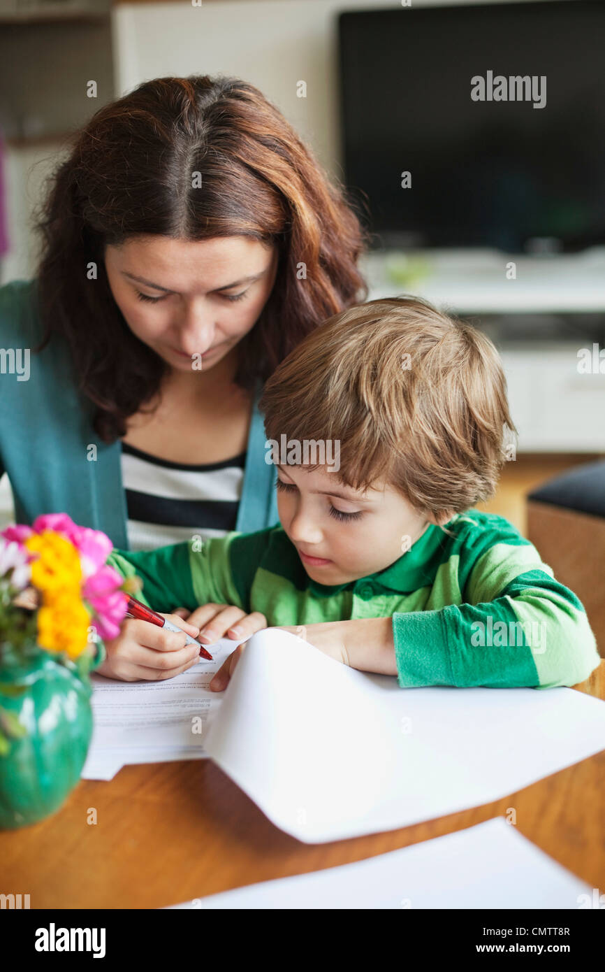 Concentrated mum and son (6-7) drawing - Stock Image