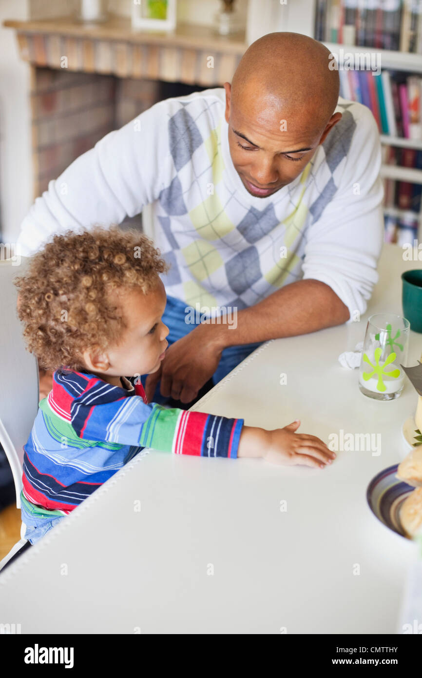 Father and boy (2-3) sitting by dining table - Stock Image