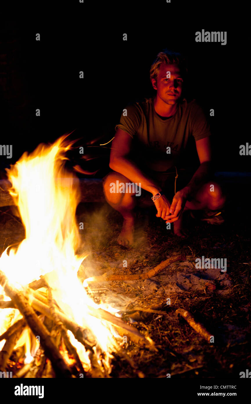 Man sitting next to fire - Stock Image