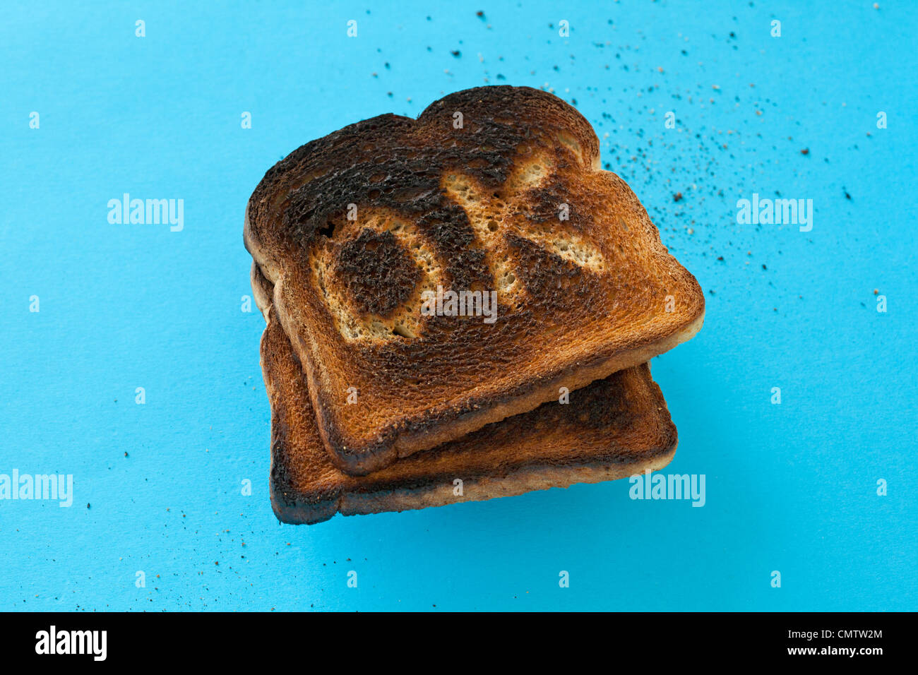 burnt toast on blue with OK scraped into it. - Stock Image