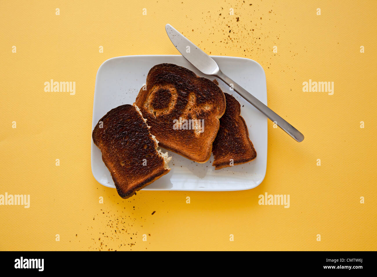 burnt toast on plate with OK carved out of it - Stock Image