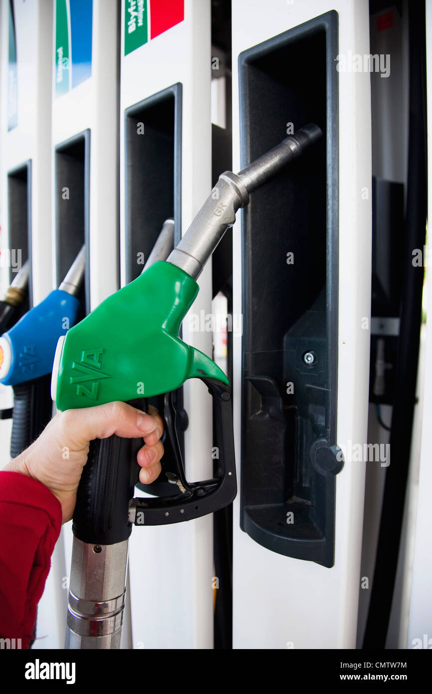 Close-up of human hand holding petrol hose - Stock Image