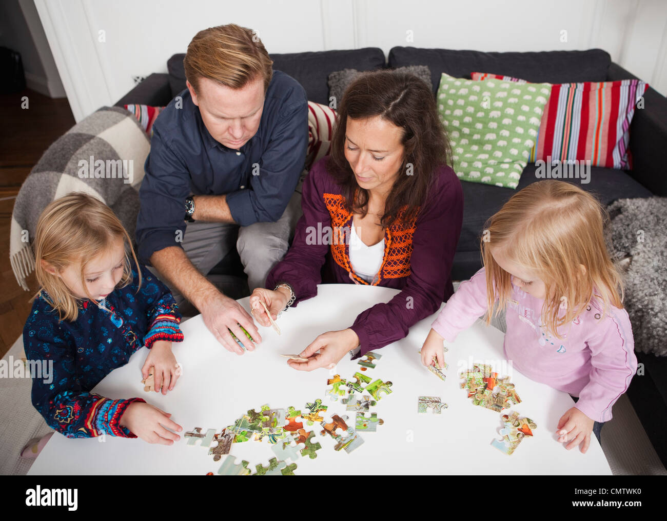 Parents and children (2-4) playing puzzle game - Stock Image