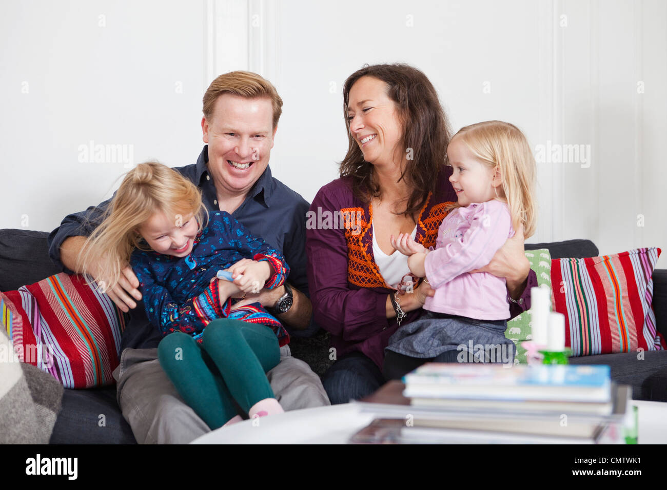 Smiling parents and daughters (2-4) in playful mood - Stock Image
