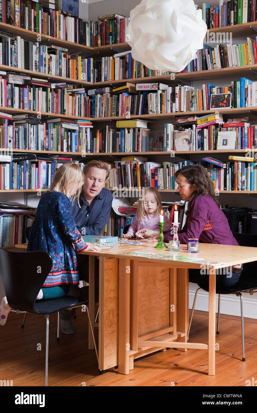 Family with two children near book shelves - Stock Image