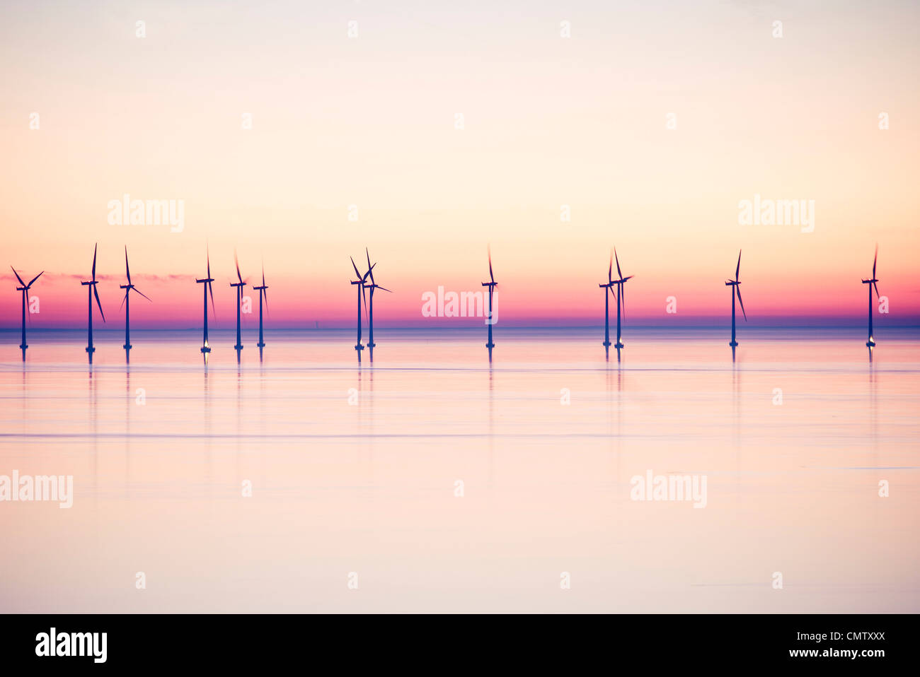Wind power stations at sea in evening - Stock Image