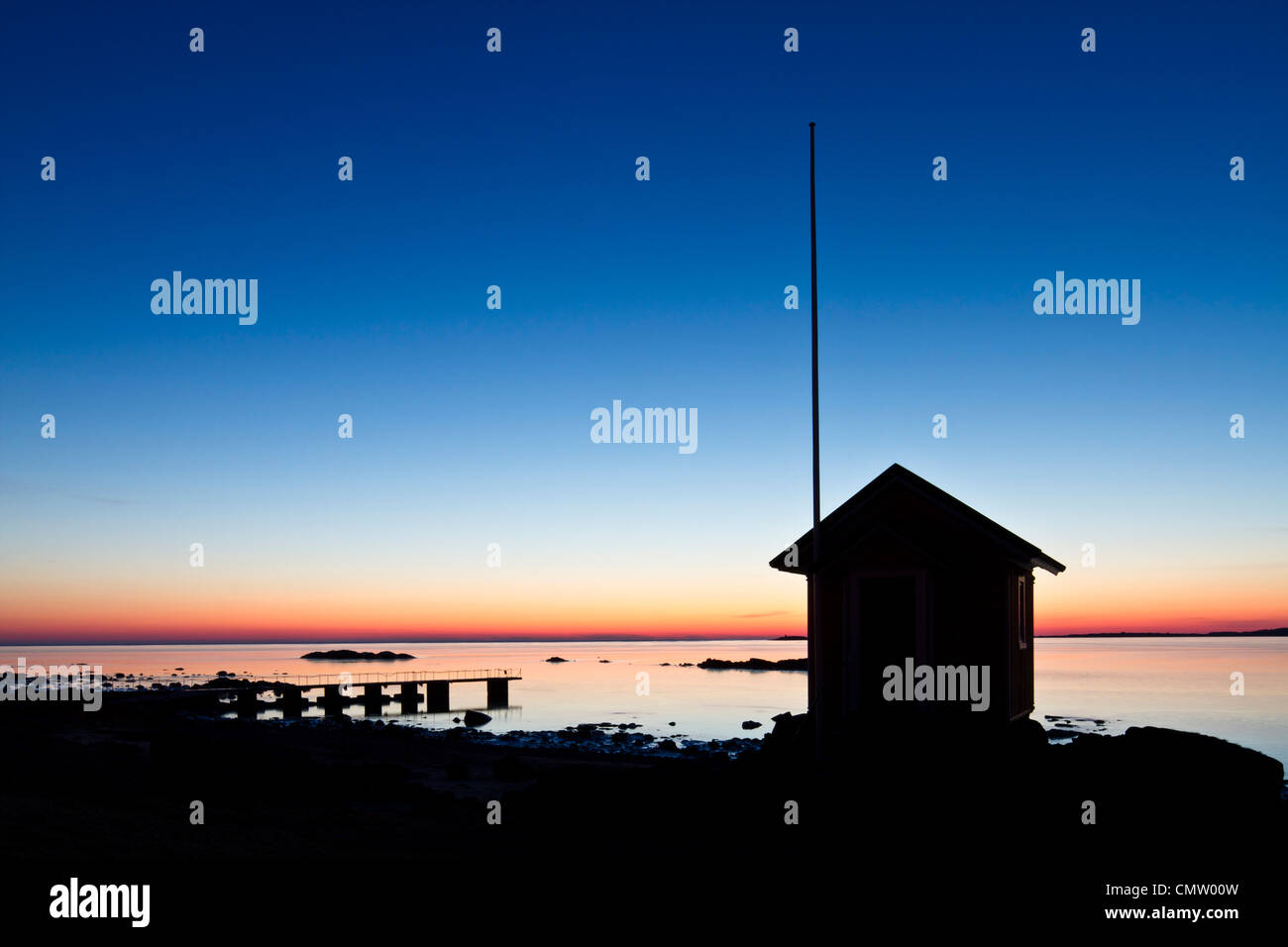 Silhouetted lodge by the sea - Stock Image
