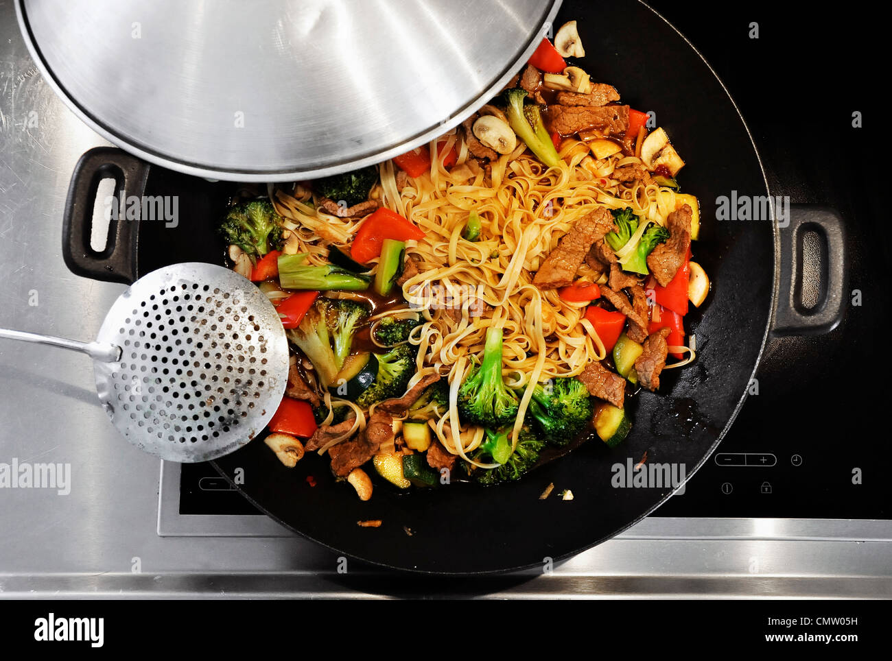 Cooking vegetable stir-fry in a wok - Stock Image