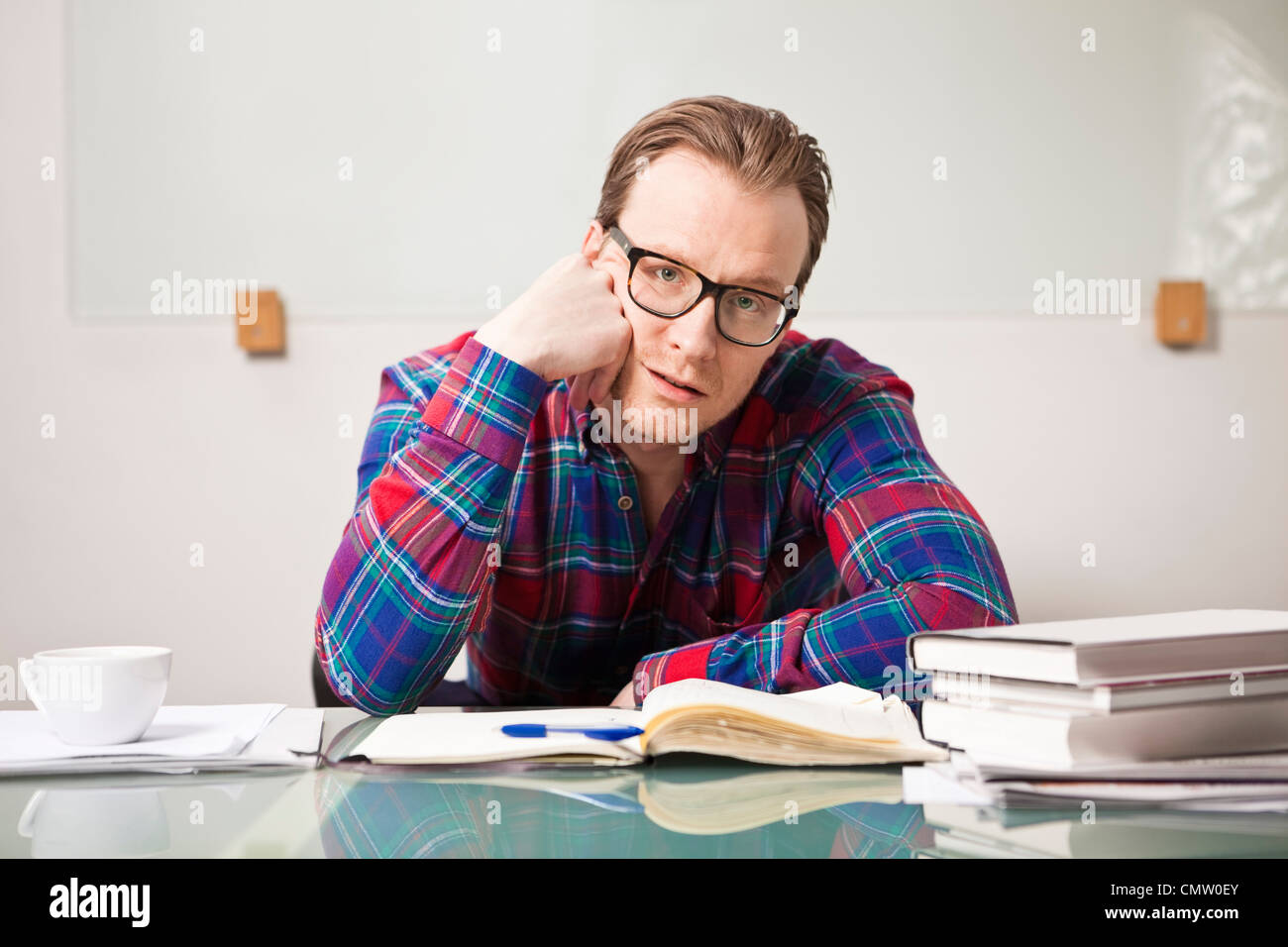 Tired businessman at his desk - Stock Image
