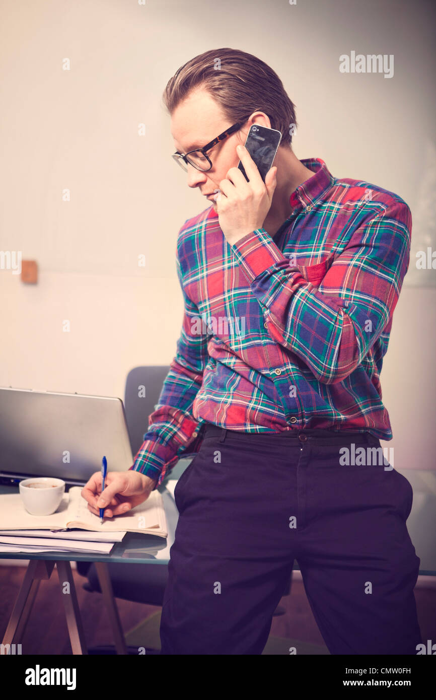 Businessman noting something while on call - Stock Image