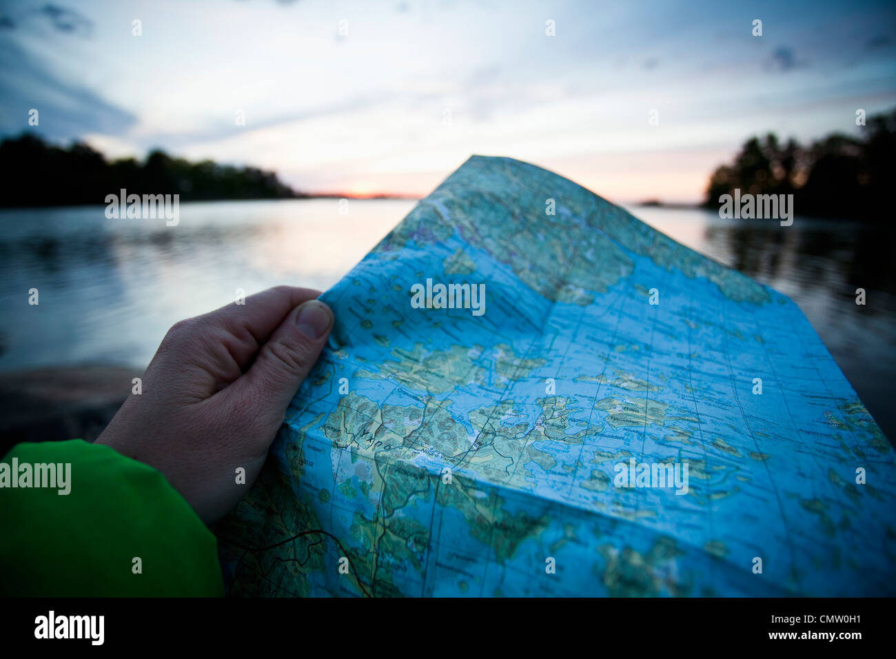 Hiker holding map nearby lake - Stock Image