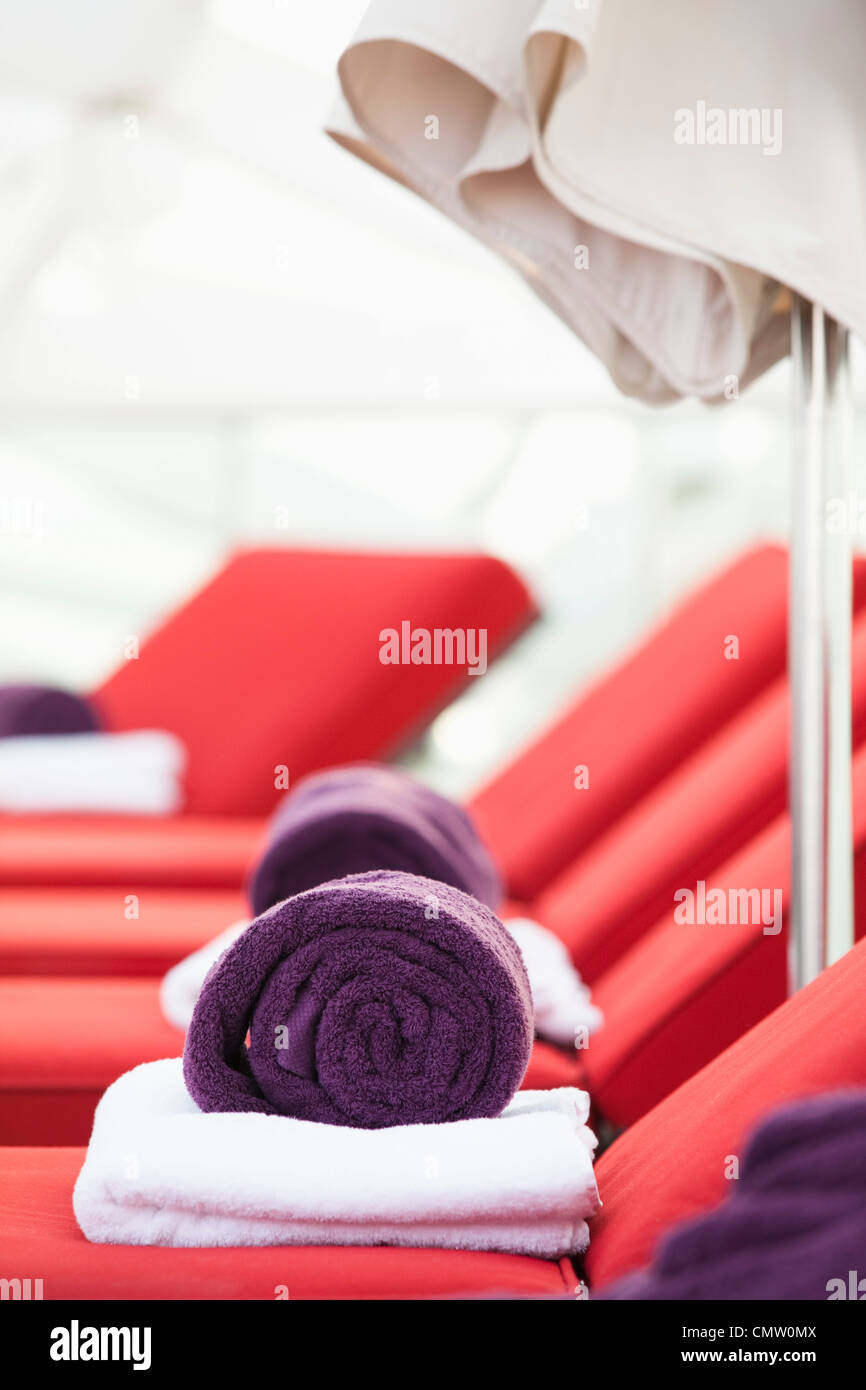 Rolled towels atop sunloungers - Stock Image