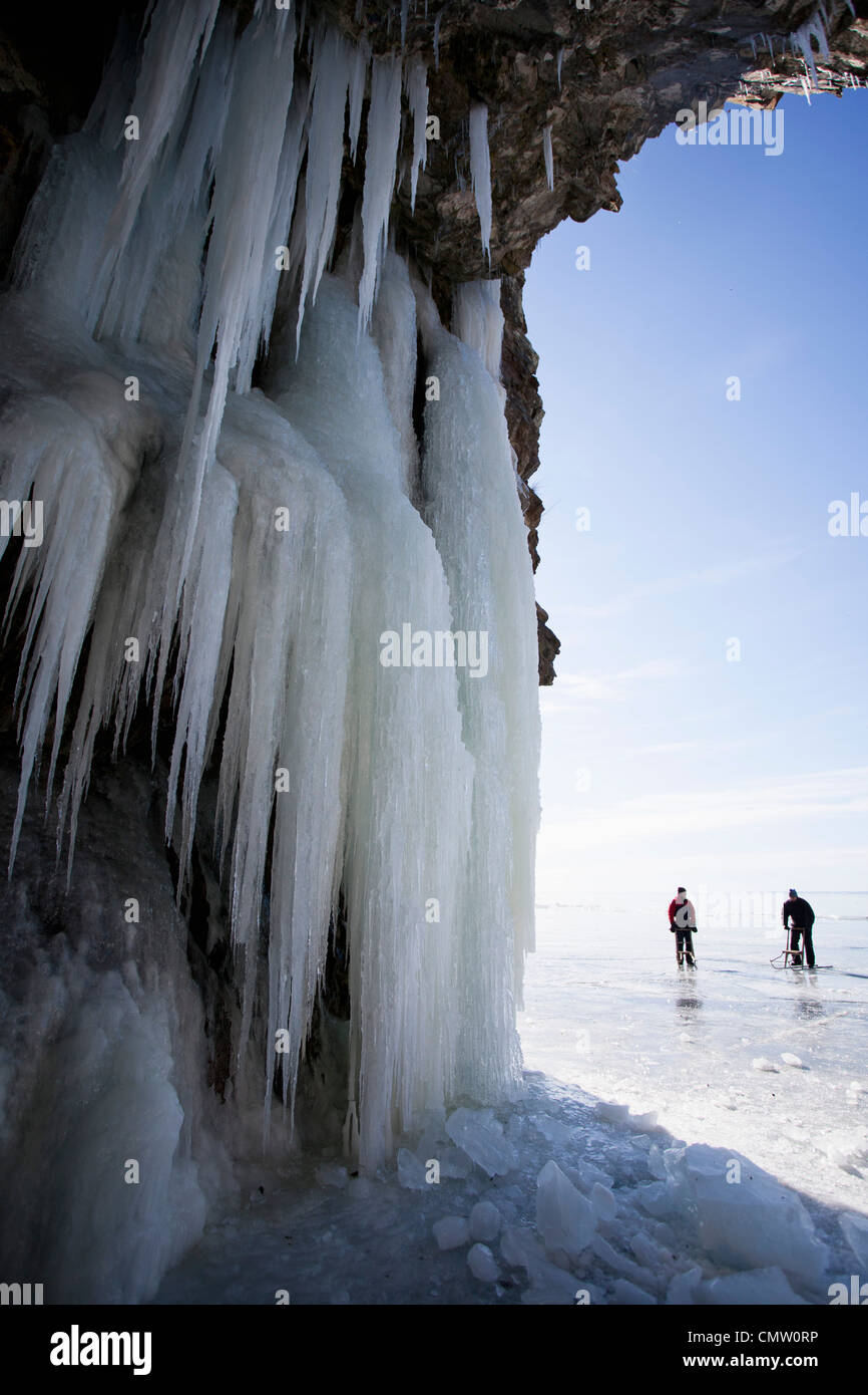 View of icicles with people hiking in background Stock Photo