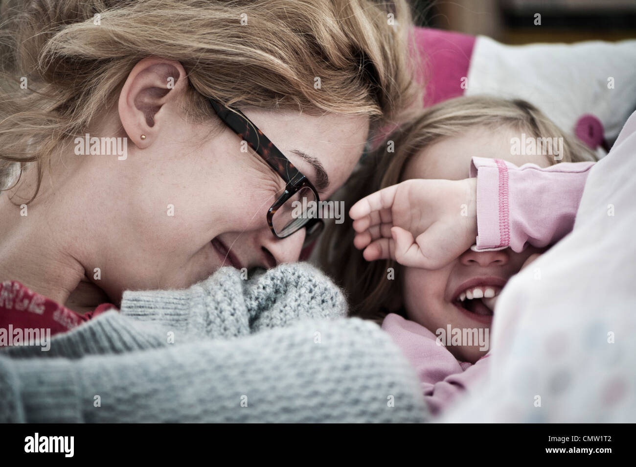 Mother and daughter in sofa - Stock Image