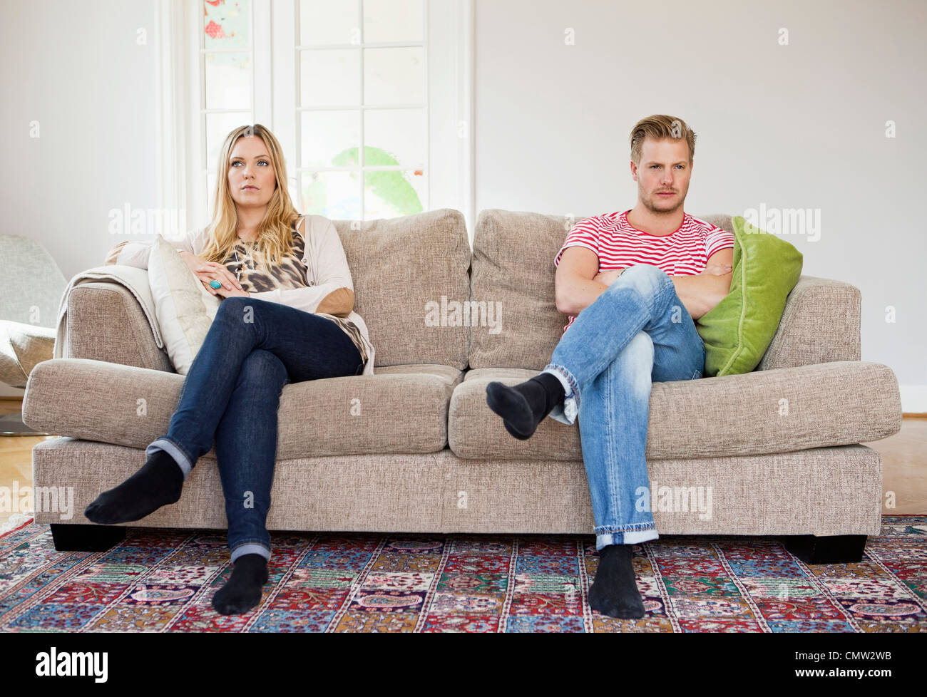 Couple looking away while sitting on sofa with arms folded Stock Photo
