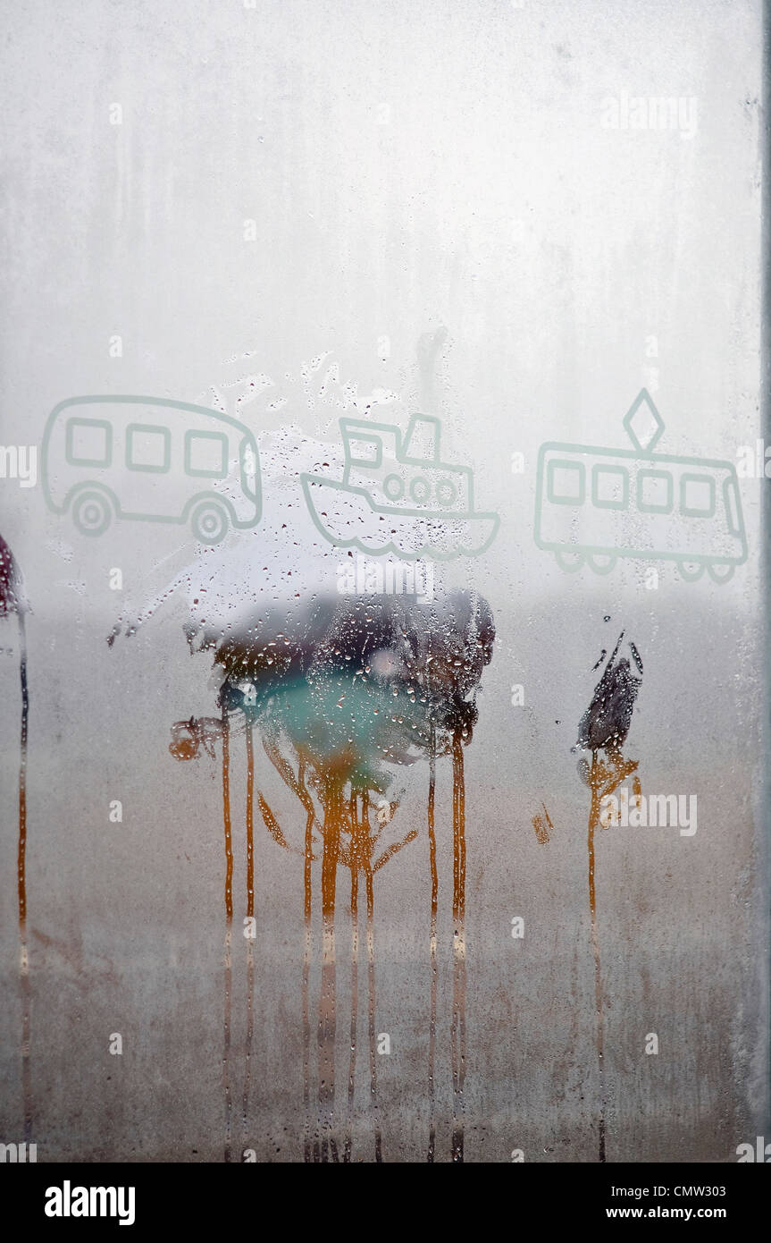 Drawings on condensate window glass - Stock Image