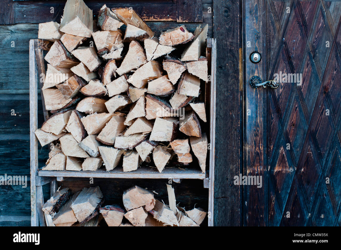 Large group of woods in shelf outside shed - Stock Image