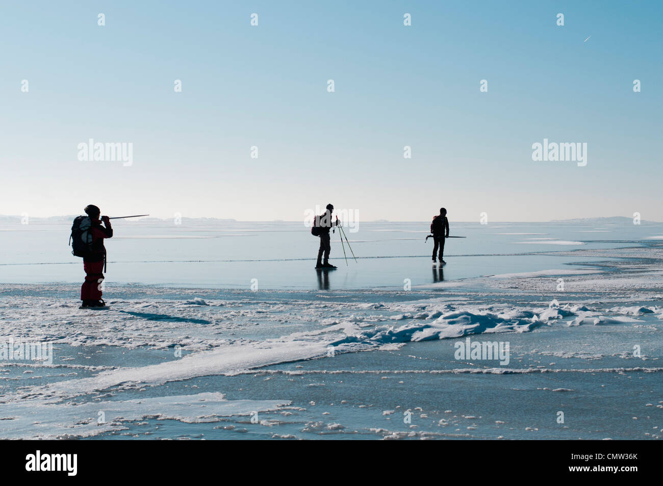 Three people on the ice against sky Stock Photo